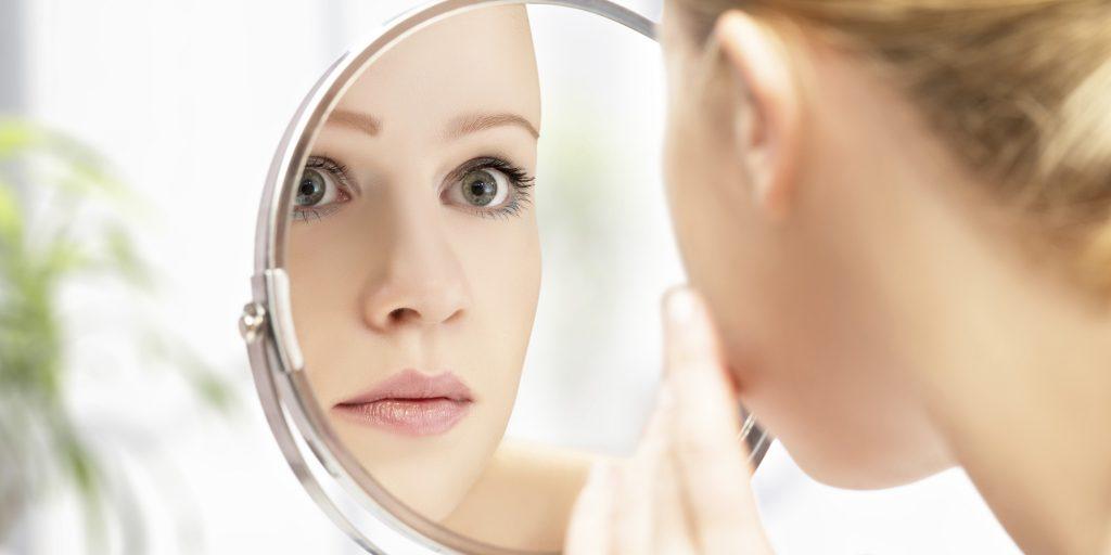 donna che si guarda allo specchio sorridendo